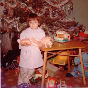 Ellen (Doyle) MacDonald in front of the Christmas tree holding one of her dolls.